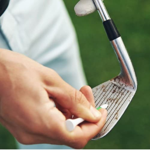 golfer cleaning golf club iron